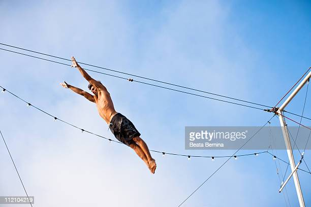 Male trapeze artist up in the air