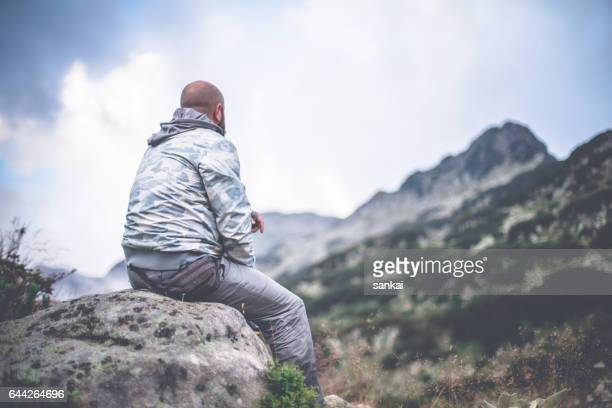 male traveler sits on a rock alone in mountains and looking on a dramatic sky - pirin national park stock pictures, royalty-free photos & images