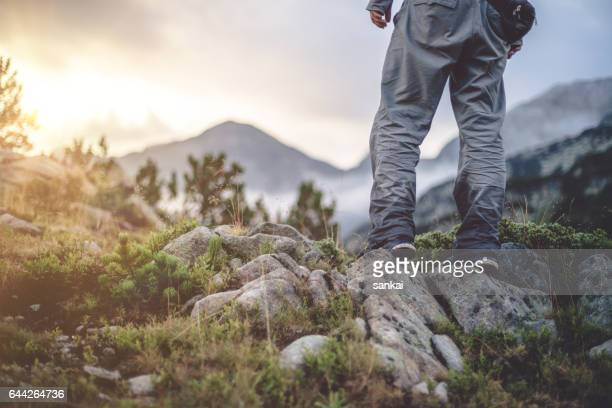 male traveler stands alone in mountains and looking ahead on a overcast sky on sunset. - pirin national park stock pictures, royalty-free photos & images