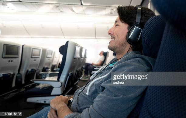 male traveler watching in-flight entertainment using headphones - arts culture and entertainment stock pictures, royalty-free photos & images