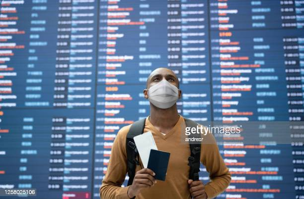 male traveler wearing a facemask at the airport - biosecurity stock pictures, royalty-free photos & images