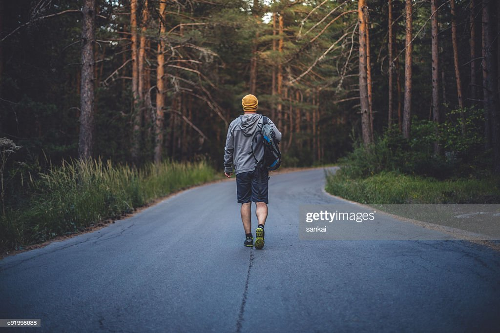 Male traveler with backpack walks forward by the road : Stock-Foto
