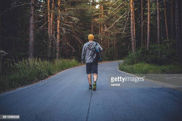 Male traveler with backpack walks forward by the road