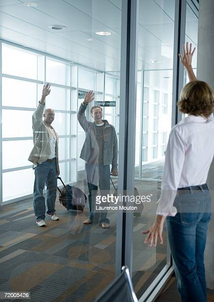 Male travelers waving to woman through window in airport