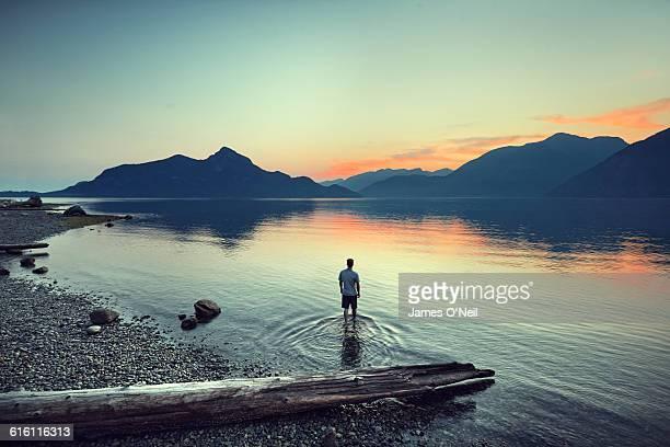 male traveller standing in water watching sunset - só um homem - fotografias e filmes do acervo
