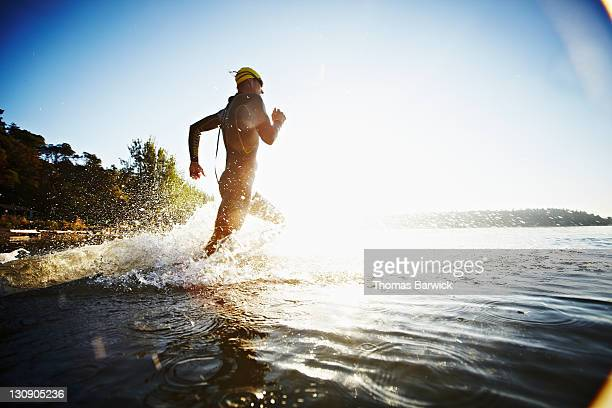 Male triathlete running into water at sunrise