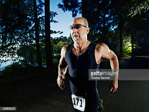 Male triathlete running race on path through woods