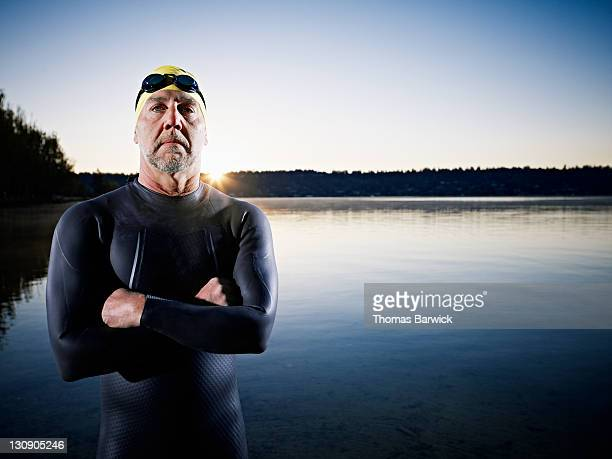 Male triathlete standing in water arms crossed