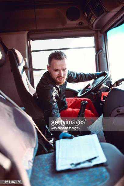 male truck driver checking address on clipboard for delivery - flammable stock photos and pictures