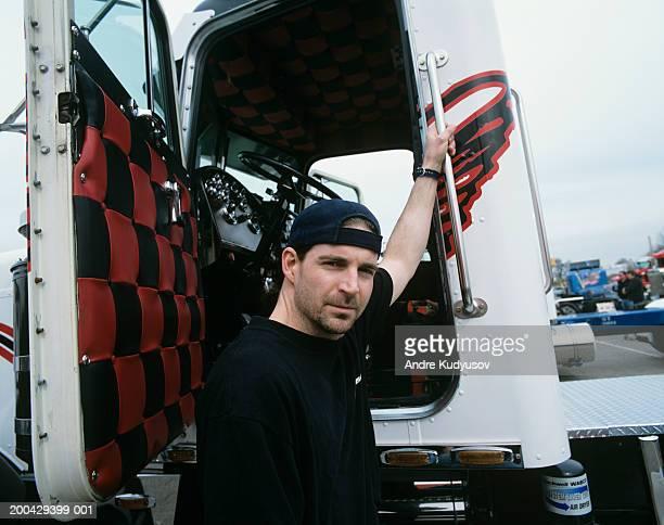 Male truck driver preparing to climb into cab of truck, portrait