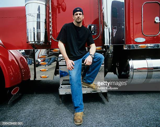 Male truck driver sitting on steps to cab of truck, portrait