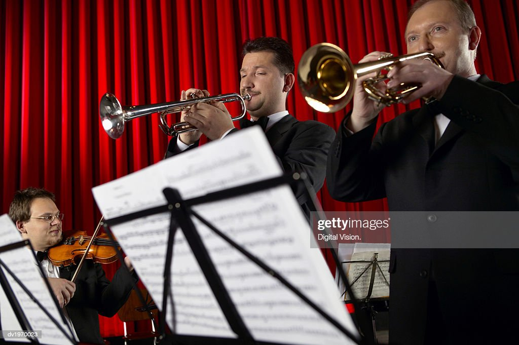 Male Trumpeters and Violinist Perform in an Orchestra : Stock Photo