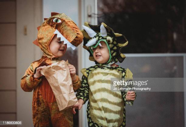 male twin toddlers dress up for halloween as dinosaurs - dinosaur stock pictures, royalty-free photos & images