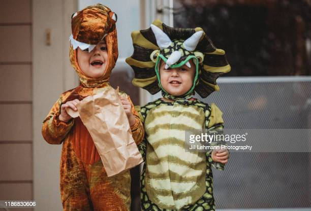male twin toddlers dress up for halloween as dinosaurs - stage costume stock pictures, royalty-free photos & images