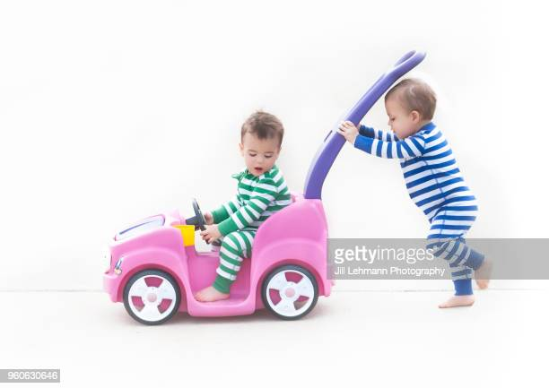 Male Twin Toddlers Push Each Other in Pink Plastic Toy Car in Pajamas