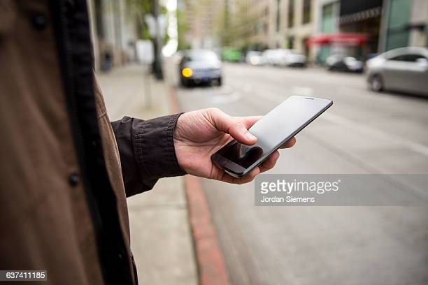 a male using a cell phone for transportation. - 焦点 ストックフォトと画像