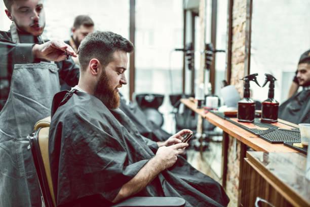 male using smartphone while getting haircut in barber shop picture id1296495726?k=6&m=1296495726&s=612x612&w=0&h=BIcNuQS FWipfJQLuShGkQJGJrdMSf288psqMufy9B4=