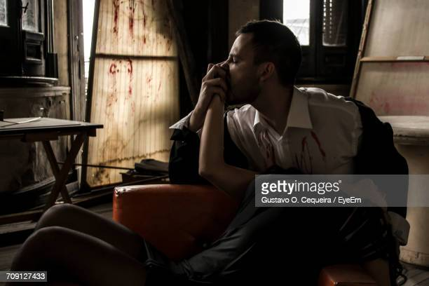 male vampire eating woman in abandoned building - cannibalism stock photos and pictures
