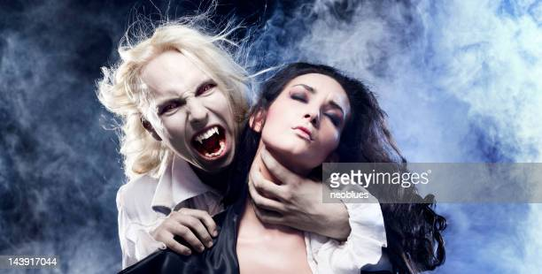 male vampire is biting a beautiful woman. - werewolf stock photos and pictures