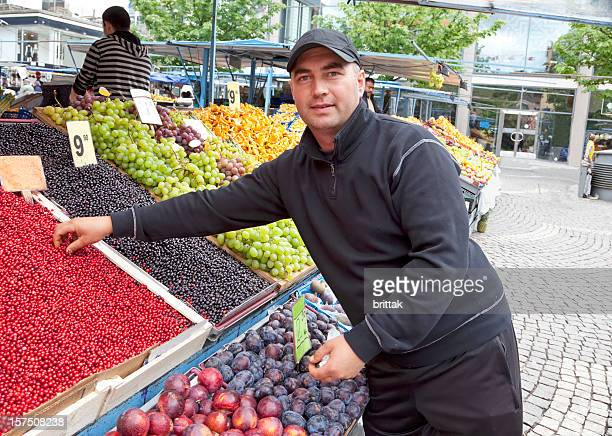 Male vendor selling berries and fruit at farmers market. Stockholm.
