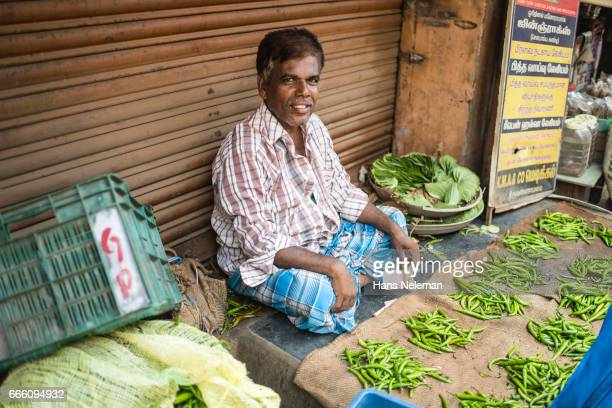 male vendor selling fresh vegetables - printed sleeve stock pictures, royalty-free photos & images