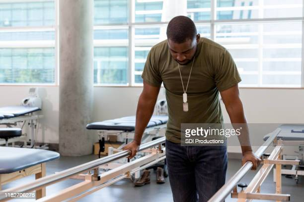 male veteran grips handrails to walk with injured leg - outpatient care stock pictures, royalty-free photos & images