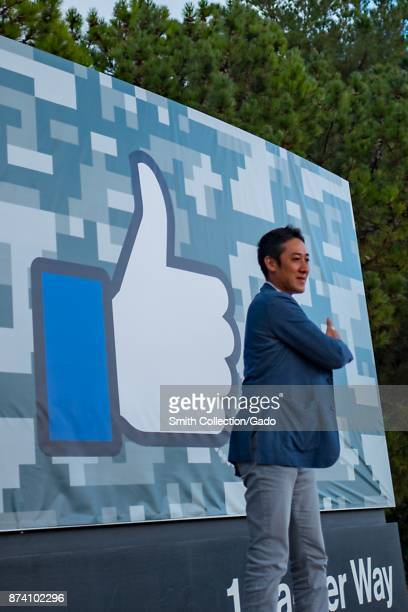 A male visitor poses and makes a 'thumbs up' gesture in front of a sign with the distinctive Facebook Thumbs Up logo at the headquarters of social...