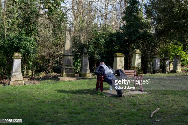 A male visitor sleeps with his head back while sitting in front of Victorian graves and memorials in south London's in south London's Nunhead...