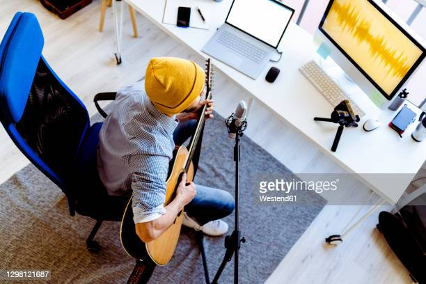 male vlogger playing guitar while live streaming on camera at recording studio - singer songwriter stock pictures, royalty-free photos & images