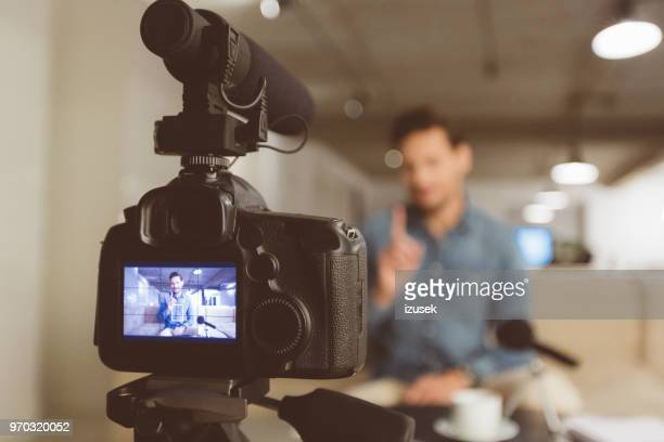 male vlogger recording content for his vlog - contented emotion stock pictures, royalty-free photos & images