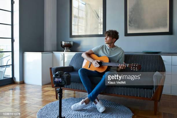 male vlogger recording guitar lesson in stylish apartment - blue film video stock-fotos und bilder