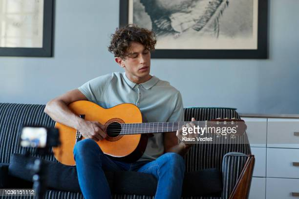 male vlogger recording guitar lesson in stylish apartment - guitarist stock pictures, royalty-free photos & images