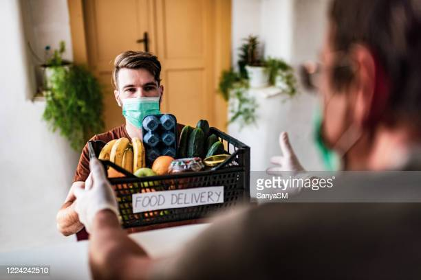 male volunteer bringing groceries to a senior man at home - charity and relief work stock pictures, royalty-free photos & images