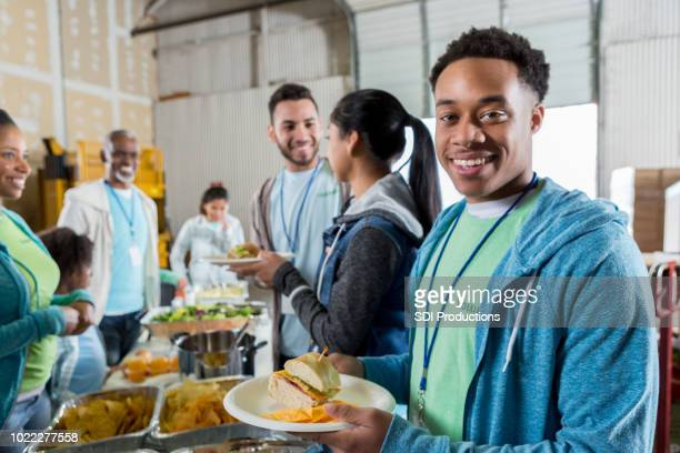 male volunteer serves meal in soup kitchen - homeless shelter stock pictures, royalty-free photos & images