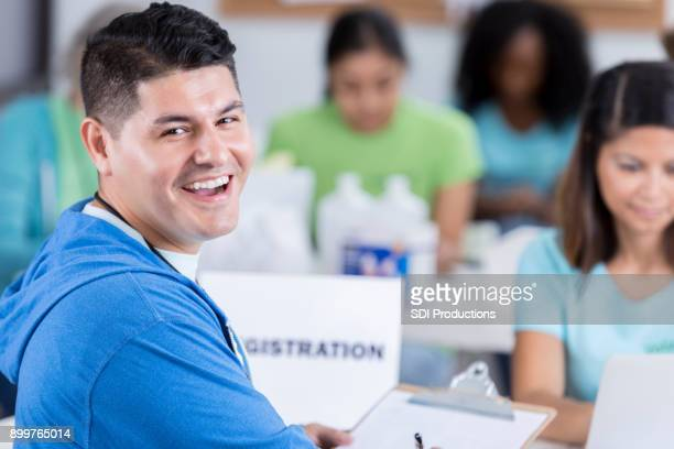 male volunteer turns to smile at the camera - register stock photos and pictures