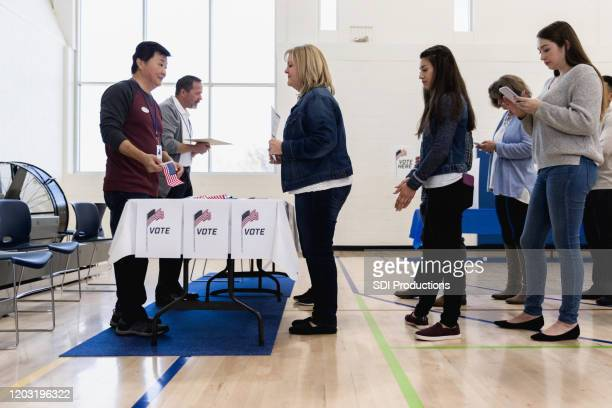 male volunteers help people waiting in line to vote - democratic party usa stock pictures, royalty-free photos & images