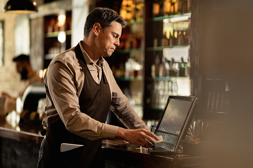 Male waiter going through orders while working at cash register in a bar. 1212064382