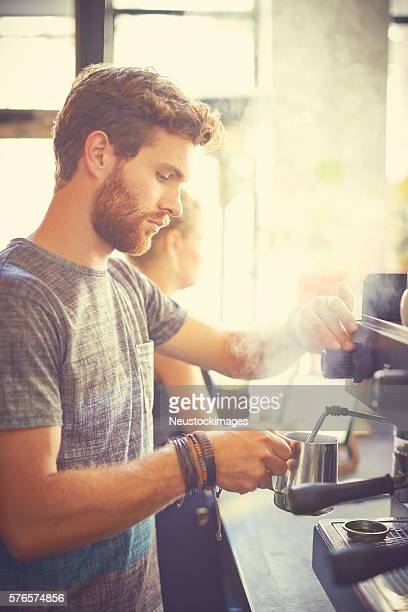 Male waiter holding milk jug in cafe
