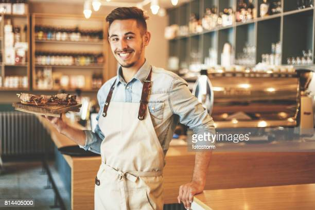 male waiter holding tray and smiling - waiter stock pictures, royalty-free photos & images