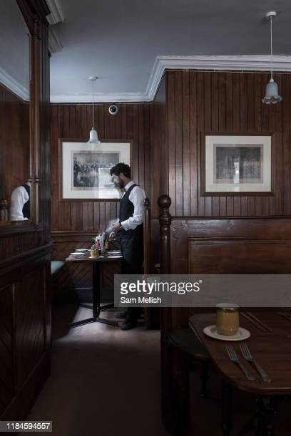 A male waiter lays a table at the Simpsons Tavern on the 24th September in East London in the United Kingdom The Simpsons Tavern is a traditional...