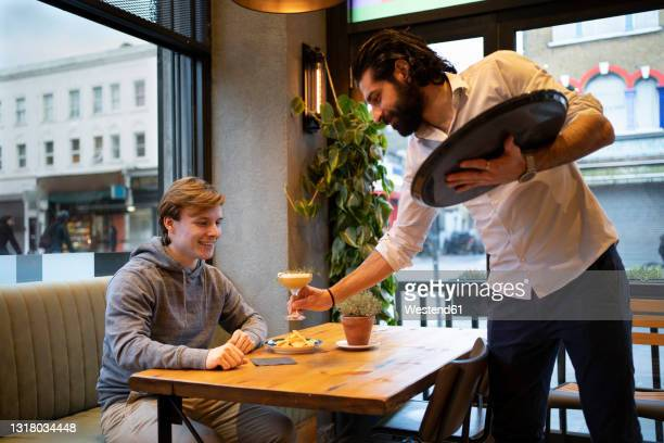 male waiter serving drink to young customer in bar - service stock pictures, royalty-free photos & images