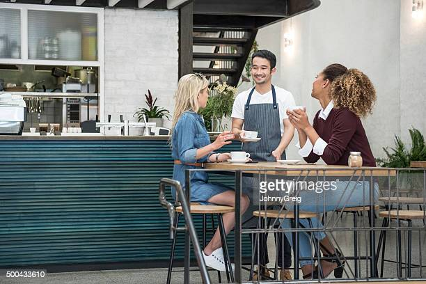 Male waiter serving two young women in cafe