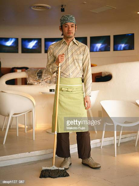 Male waiter standing in a cafe, holding a broom
