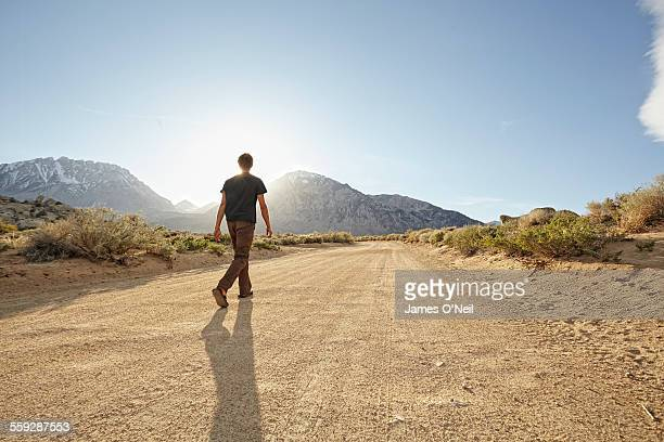 male walking up dirt road into the light - remote location stock pictures, royalty-free photos & images