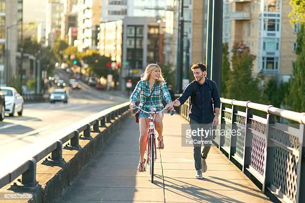 Male walks while girlfriend rides a bike downtown