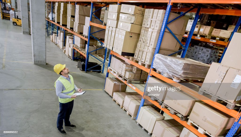 male warehouse employee doing inventory check in warehouse stock