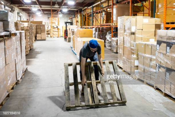 a male warehouse worker attempting to lift a pallet in an unsafe way that could injure his back - lower back stock pictures, royalty-free photos & images