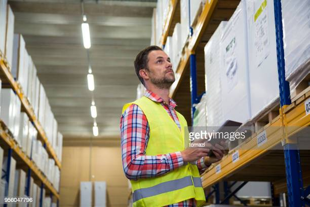 Male warehouse worker checking codes