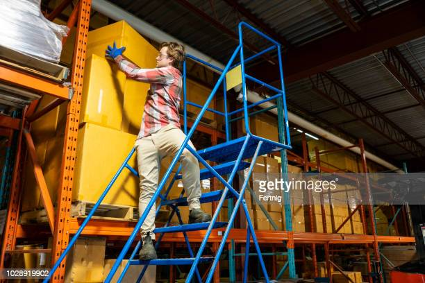 a male warehouse worker climbs a rolling ladder incorrectly. - danger stock photos and pictures
