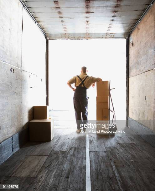 male warehouse worker in freight truck with boxes - sack barrow stock pictures, royalty-free photos & images